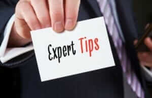 A businessman holding a business card with the words, Expert Tips, written on it. How to get more website traffic