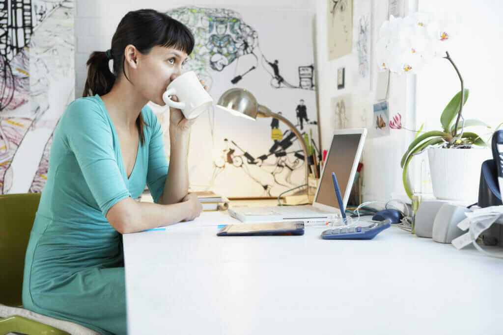 woman at her desk drinking coffee learning how to make money with affiliate marketing without a website