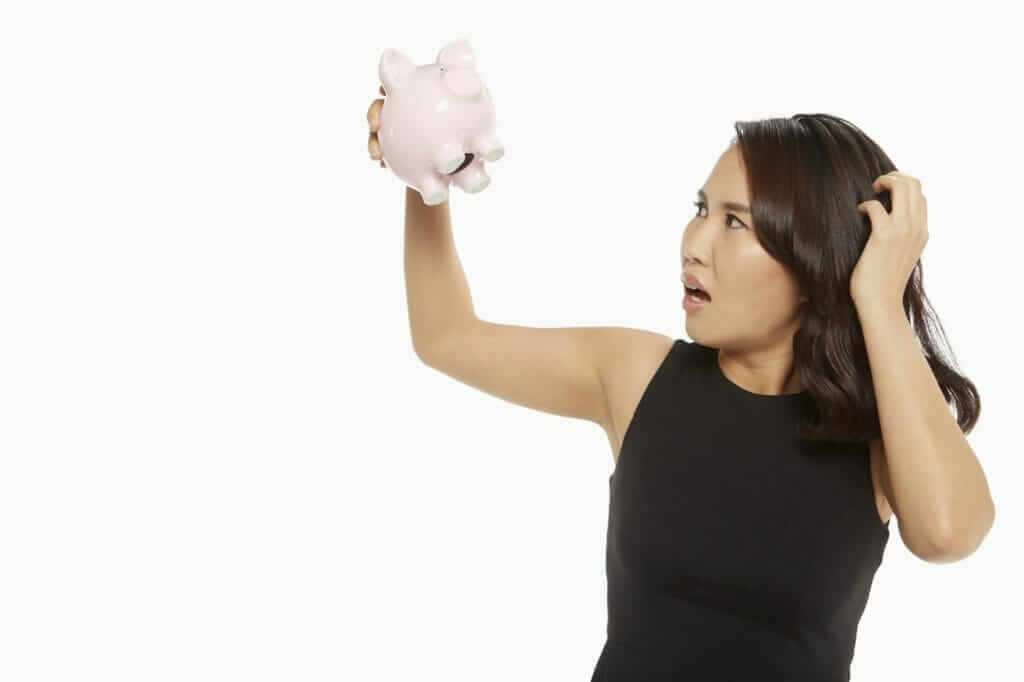 Woman is tired of being broke and looking at piggy bank